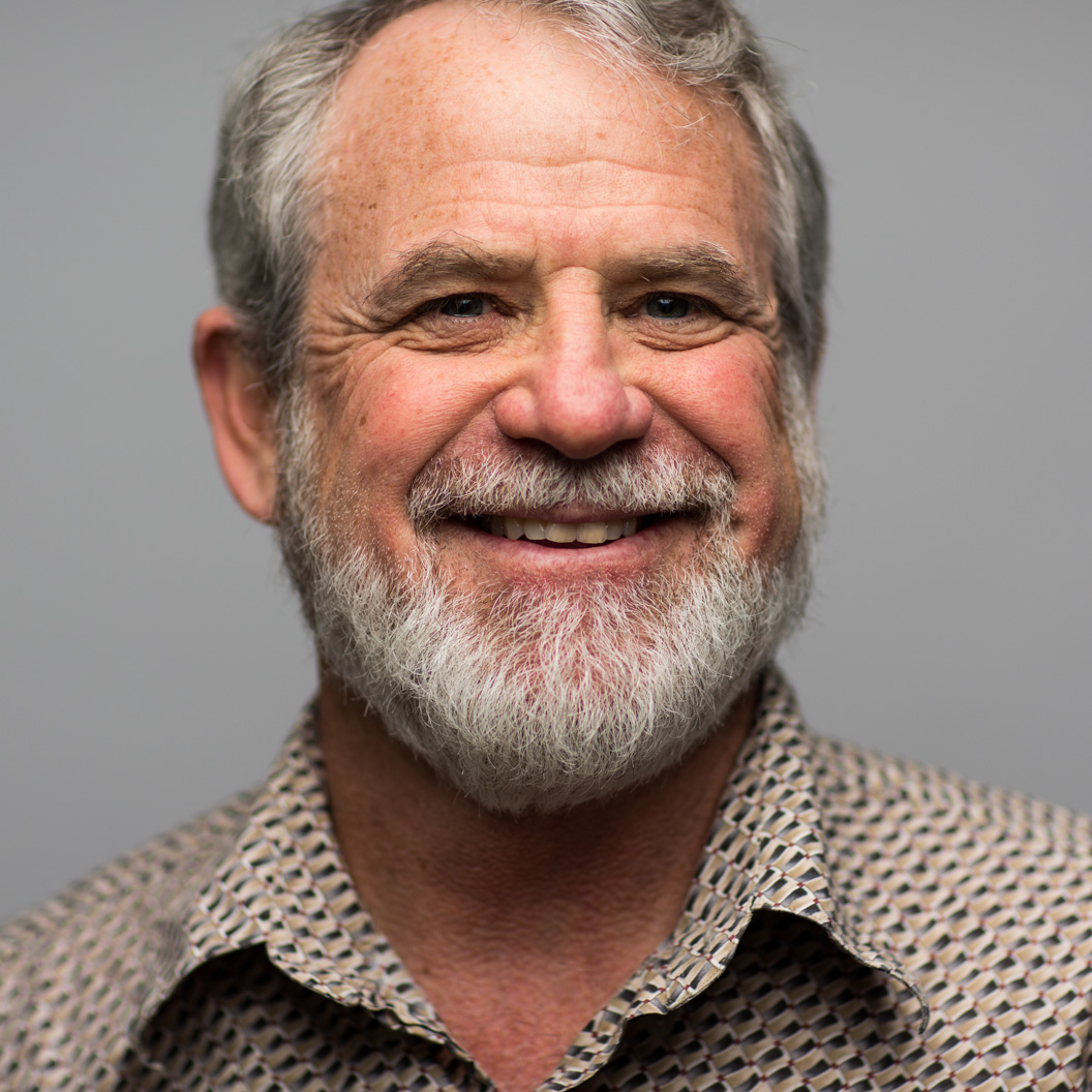 A middle aged man with a beard and a beige collared shirt smiles on a grey studio backdrop
