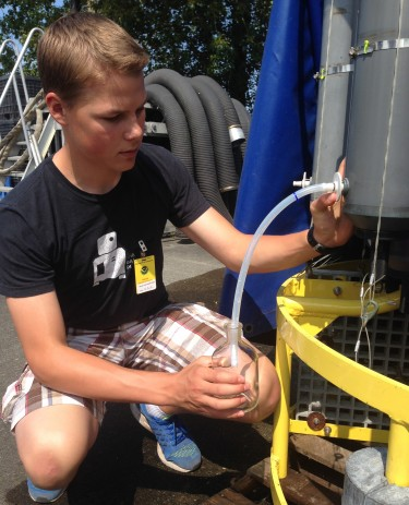 University Prep student Jacob Richey fills a sample bottle during a summer training session.