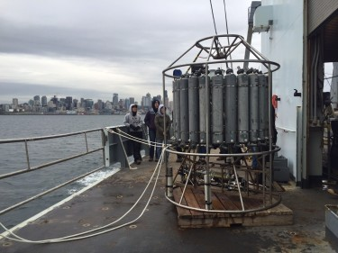 Students watch a CTD being deployed near downtown Seattle and the mouth of the Duwamish River. CTDs measure conductivity, temperature, and depth of the ocean.
