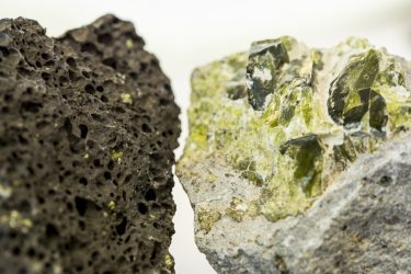 "Basalt, the dominant volcanic rock along the Pacific Ocean's ""Ring of Fire,"" is considered a melting product of the Earth's mantle. On the left is vesicular basalt, in which dissolved gases formed bubbles as the magma decompressed. On the right is a magnesium-rich olivine crystal that formed inside the volcano, embedded in a fine-grained solid. Detailed chemical analyses found that magnesium in arc volcano basalt shows surprising traces of the descending ocean crust."
