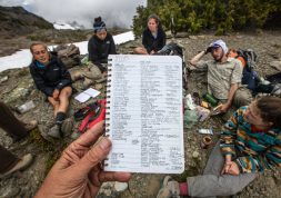 Journal pages list all the species of plants the UW Environmental Studies class has seen by the penultimate day of their backpacking trip in the Olympic National Park backcountry. Here, the group takes a break at Grand Pass.