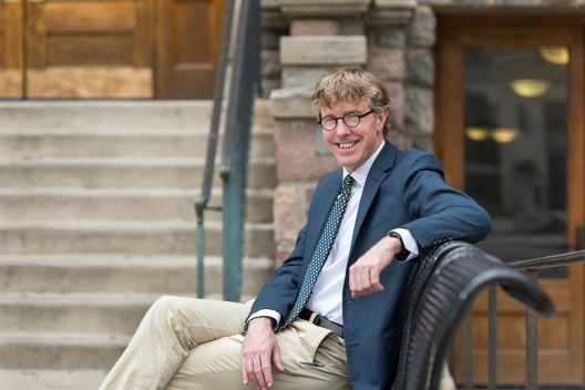 Man with blonde hair and dark-rimmed glasses, wearing a blue sport coat, khaki pants and a tie sits on a bench. He is smiling at the camera, and has one arm propped up on the back of the bench. Stairs are in the background.