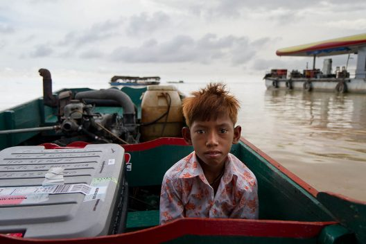 A young boy sits in a boat on top of brackish waters, another boat in the background.