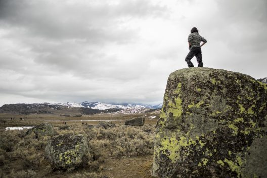 A photo of a University of Washington undergrad stands on a tall boulder. She watches other students hike through patchy snow in Yellowstone National Park.