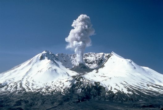 The mountain's crater, covered in snow, lets out a small plume against a dark blue sky.