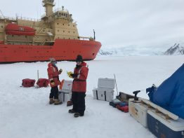 Hannah Dawson and Sussan Rundell with their gear and the R/V Nathaniel B. Palmer in the background.