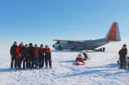 Hercules Dome field team poses next to a plane