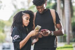 A man and a woman looking standing close together and looking at their phones