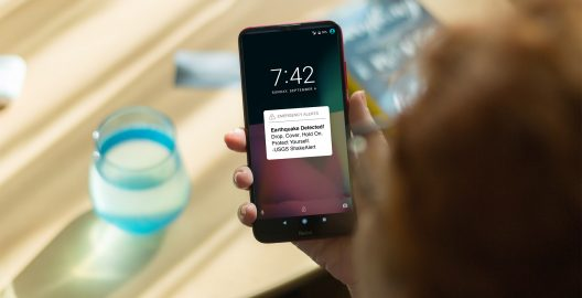 """A hand holds a phone lock screen with an emergency alert that reads """"Earthquake detected! Drop, cover, hold on. Protect yourself -USGS ShakeAlert"""""""