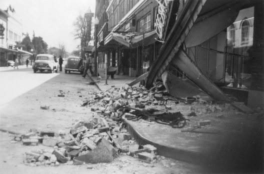 A black in white photo of rubble and debris spilling out onto the street.