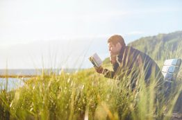 Man reading book on bench with grass waving in foreground